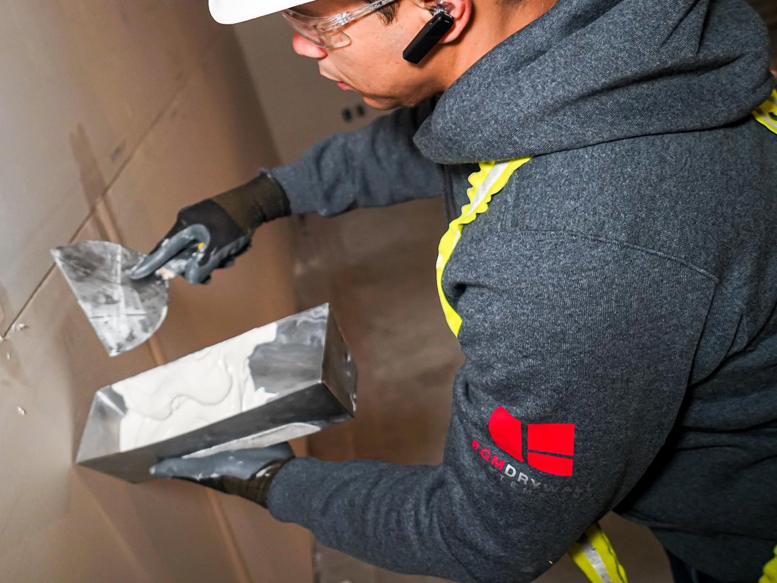 EGM Drywall Employee Mudding Wall in Edmonton